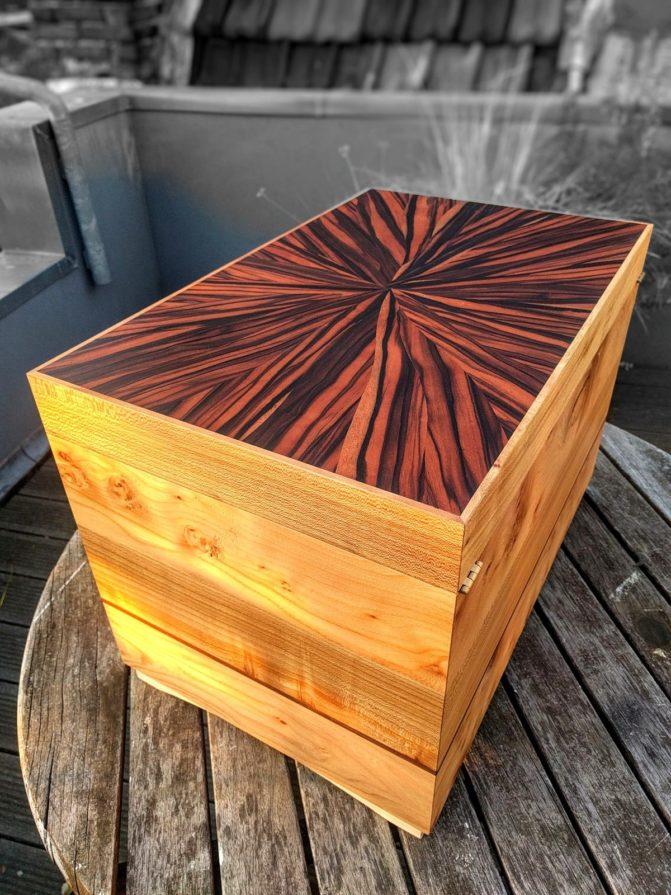 Kist van massiefhout met fineer aan bovenzijde
